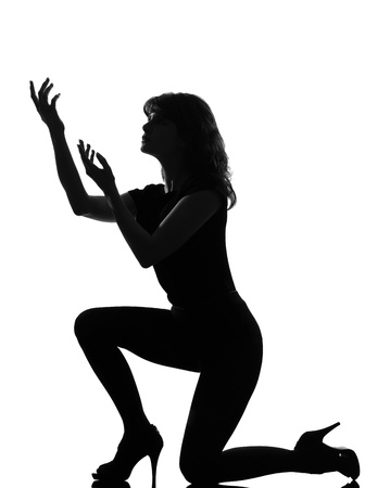 to implore: full length silhouette in shadow of a young woman kneel pray implore  in studio on white background isolated LANG_EVOIMAGES