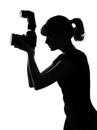 Portret silhouet in de schaduw van een jonge vrouw-fotograaf die houden van een camera in een studio op een witte achtergrond, geïsoleerd