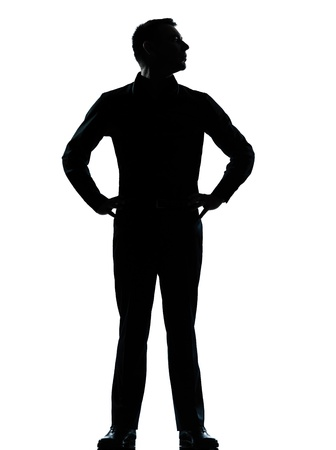 one caucasian business man silhouette standing hands on hips Full length in studio isolated on white background