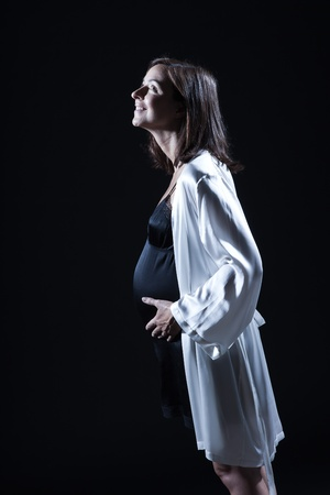 beautiful smiling caucasian pregnant  woman portraitt   touching her belly in nightie on studio isolated black background Stock Photo - 11633563