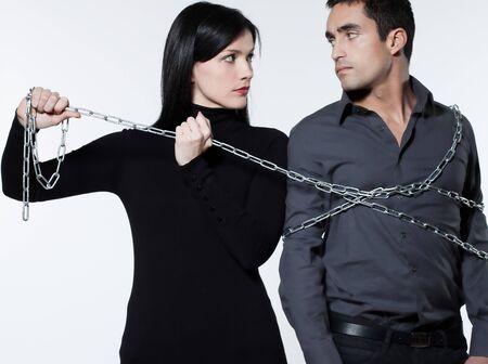 desconfianza: mujer de unirse a su hombre con una cadena en el fondo blanco