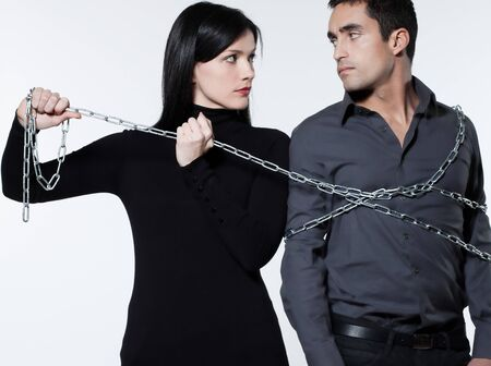 distrust: woman binding his man with a chain on white background