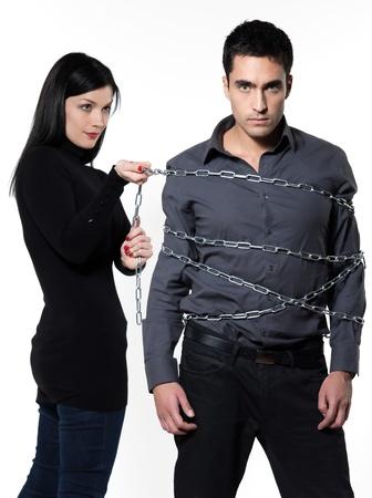 dominacion: mujer vinculantes a su hombre con una cadena en el fondo blanco Foto de archivo