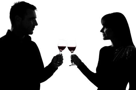 couple lit: one caucasian couple man and woman drinking red wine toasting in studio silhouette isolated on white background