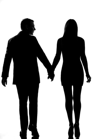 walk in: rear view one lovers caucasian couple man and woman walking hand in hand in studio silhouette isolated on white background