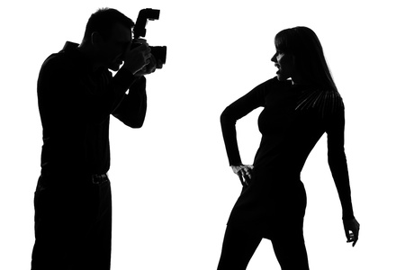 one caucasian  couple man photographer photographing and woman fashion model posing in studio silhouette isolated on white background