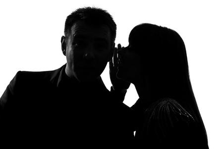 fofoca: silhueta de um casal caucasiano homem e uma mulher sussurrando no ouvido no est�dio isolado no fundo branco