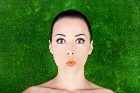 caras emociones: Primer plano de un bello retrato de belleza de la mujer sorprendida en el fondo de la hierba de estudio Foto de archivo