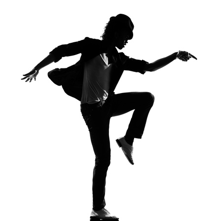 break dancing: full length silhouette of a young man dancer dancing funky hip hop r&b on  isolated  studio white background