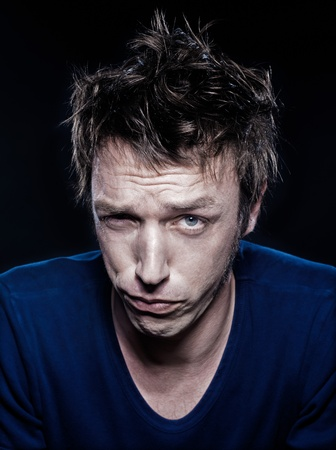 hesitancy: studio portrait on black background of a funny expressive caucasian man frowning doubtful Stock Photo