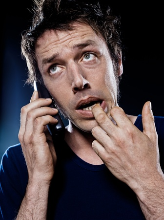 studio portrait on black background of a funny expressive caucasian man phoning anxious Stock Photo - 11634539