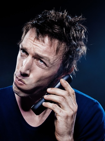 studio portrait on black background of a funny expressive caucasian man phoning anguish Stock Photo - 11634506