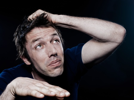 studio portrait on black background of a funny expressive caucasian man looking up scared photo