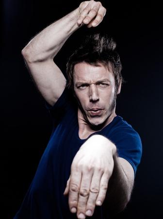 handsign: studio portrait on black background of a funny expressive caucasian man fight posture