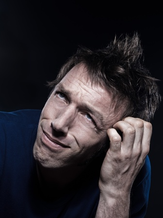 puckering: studio portrait on black background of a funny expressive caucasian man puckering hesitant