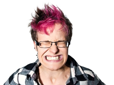 Close-up portrait of a young expressive irritated woman clenching teeth in studio on white isolated background photo