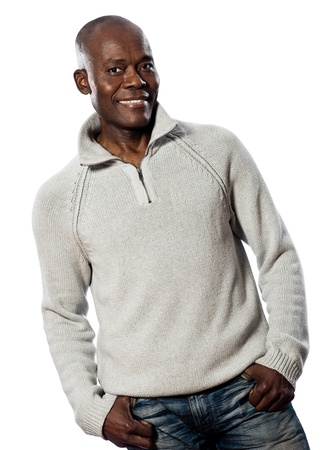 african background: Casual mature afro American man standing smiling in studio with hands in pocket on isolated white background