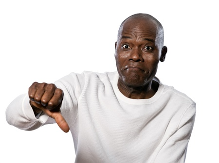 rejection sad: Portrait of a displeased afro American man showing thumbs down sign in studio on white isolated background Stock Photo