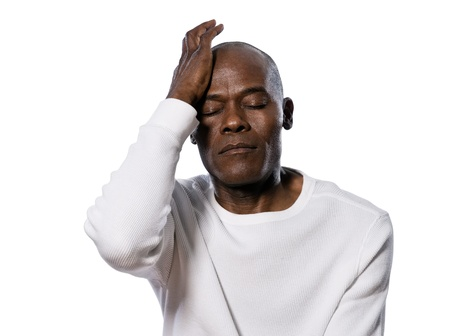 despair: Close-up of a serious afro American man with headache in studio on white isolated background Stock Photo