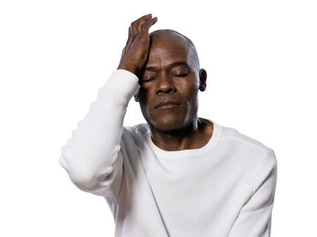hoofdpijn: Close-up van een ernstige Afro-Amerikaanse man met hoofdpijn in de studio op witte geïsoleerde achtergrond Stockfoto