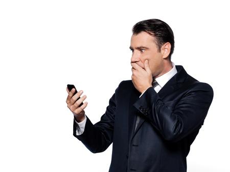 handsome caucasian man looking at phone amazed portrait isolated studio on white background photo