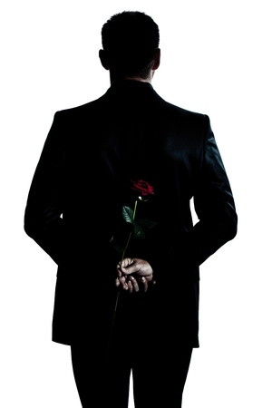 one caucasian backside man holding a rose flower portrait silhouette in studio isolated white background photo