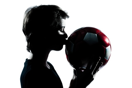 one caucasian young teenager silhouette boy or girl kissing soccer football portrait in studio cut out isolated on white background photo