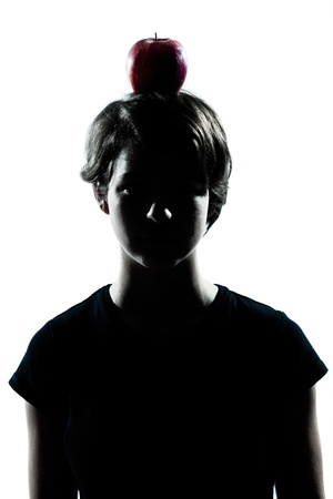 one caucasian young teenager silhouette boy or girl with an apple on his head portrait in studio cut out isolated on white background Stock Photo - 11766387
