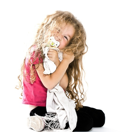 one caucasian little girl hugging blanket pacifier miling cheerful sitting on the floor isolated studio on white background photo