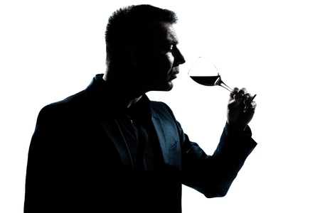 red wine glass: one caucasian man portrait silhouette smelling red wine glass in studio isolated white background