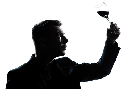one caucasian man portrait silhouette tasting  looking at his glass of red wine in studio isolated white background photo