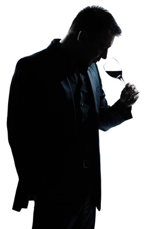 wine tasting: one caucasian man portrait silhouette smelling red wine glass in studio isolated white background