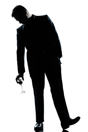 drunken: one caucasian man full length silhouette  drunk holding a glass of red wine in studio isolated white background