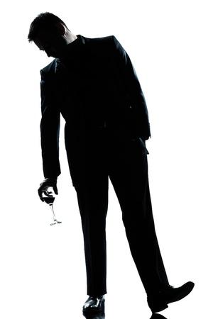 borracho: una silueta de hombre caucásico de longitud completa bebido con un vaso de vino tinto en el estudio de fondo blanco aisladas Foto de archivo