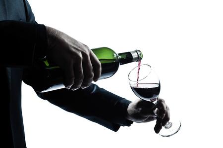 isol� sur fond blanc: un homme caucasien d�tail les mains verser le vin rouge dans une silhouette de verre dans studio isol� sur fond blanc