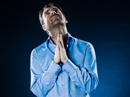 plead: caucasian man unshaven praying portrait isolated studio on black background