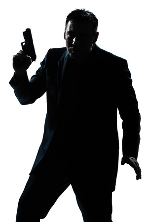 one caucasian spy criminal policeman detective man holding gun portrait silhouette in studio isolated white background Stock Photo - 11753094