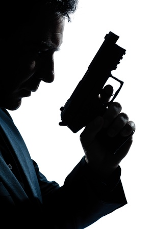 one caucasian spy criminal policeman detective man holding gun portrait silhouette in studio isolated white background Stock Photo