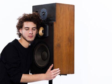 studio portret van een blanke jonge man luisteren naar muziek liefhebber met luidsprekertelefoon geïsoleerd op witte achtergrond