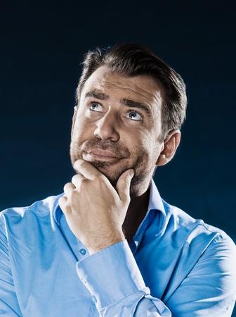 hesitancy: caucasian man unshaven thinking suspicious portrait isolated studio on black background