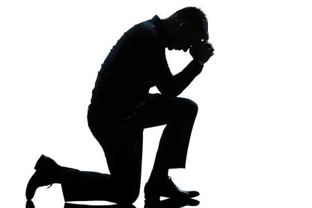 ひざまずく: 1 つの白人男性折り敷きの悲しみ studio 分離した白い背景のフルの長さシルエットを祈って