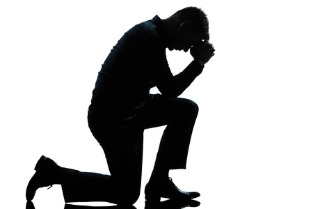 one caucasian man kneeling sadness praying full length silhouette in studio isolated white background photo