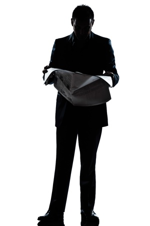 one caucasian man standing reading newspaper  full length silhouette in studio isolated white background Stock Photo - 11610301