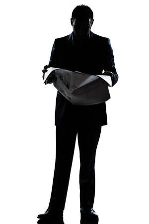 periodicos: un hombre cauc�sico de pie la lectura de peri�dicos silueta de cuerpo entero en el estudio de fondo blanco aisladas Foto de archivo