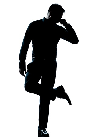 one caucasian man  looking at his shoes unpleasant smell full length silhouette in studio isolated white background photo