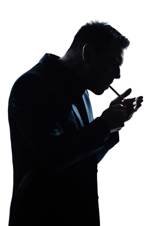 man smoking: one caucasian man portrait smoking lighting cigarette silhouette in studio isolated white background