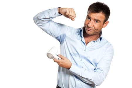 hairdryer: one caucasian man with sweat stain perspire drying shirt with hair dryer in studio isolated on white background Stock Photo