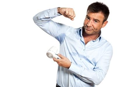 transpiration: un homme caucasien avec la chemise transpirer sueur tache de s�chage avec s�che-cheveux en studio isol� sur fond blanc Banque d'images