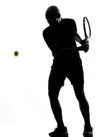 backhand: el hombre africano afro americano jugando al tenis jugador de rev�s, en el estudio aislado en fondo blanco