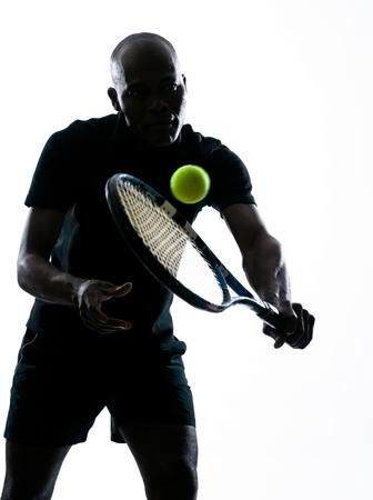 jugando tenis: el hombre africano afro americano jugando al tenis jugador de revés, en el estudio aislado en fondo blanco